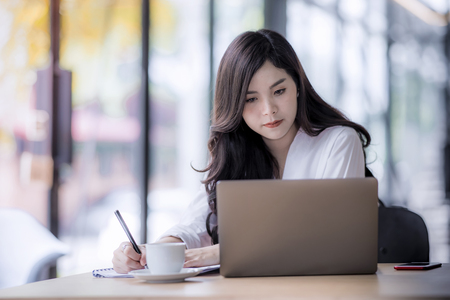Foto de young asian business woman using laptop and writing on notebook, woman officer hard working communicate with customer and record - Imagen libre de derechos