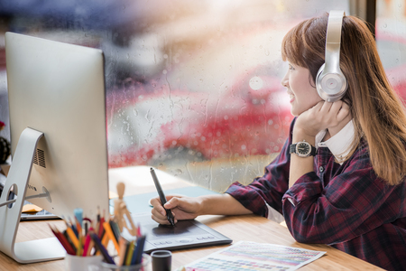 Photo pour beautiful young woman designer listening music with headphone while using pen mouse working in office with raining day outside - image libre de droit