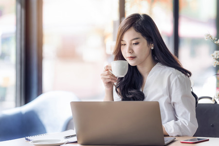 Foto de Young business asian woman holding cup of coffee and looking at laptop,woman officer  drink coffee at break time. - Imagen libre de derechos
