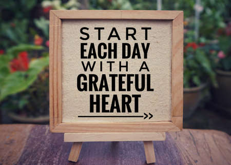 Photo pour Motivational and inspirational quote - 'Start each day with a grateful heart' written on a framed white paper. Vintage styled background. - image libre de droit