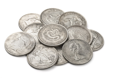 Foto de Heap of old silver coins isolated on white - Imagen libre de derechos