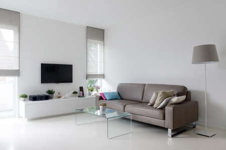 Photo for White living room with taupe leather sofa and glass table - Royalty Free Image