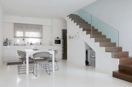 Photo pour white kitchen and dining room with white epoxy floor and wooden stairs - image libre de droit