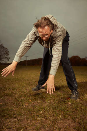 Foto per Aging older man exercising in sportsuit outdoor on meadow - Immagine Royalty Free