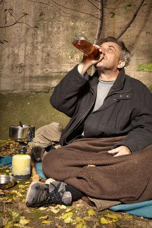 Foto de Ugly pauper man living outdoor drinking alcoholic beverages - Imagen libre de derechos
