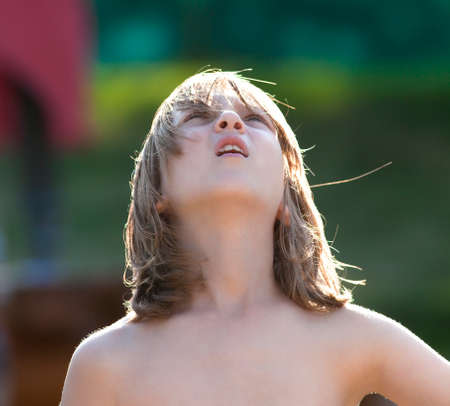 Photo pour Portrait of a Boy with Blond Hair Looking Up Outdoors - image libre de droit