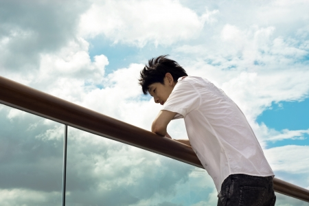 Sad boy hand on the handrail and sky background