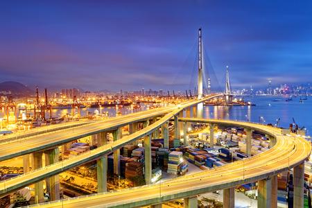 Foto de Container Cargo freight ship with working crane bridge in shipyard under Stonecutters highway bridge at sunset for Logistic Import Export, Hong kong - Imagen libre de derechos