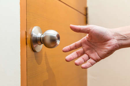 Photo pour male hand reaching out to grab a door knob, good for coming home, home safety or intruder concept - image libre de droit