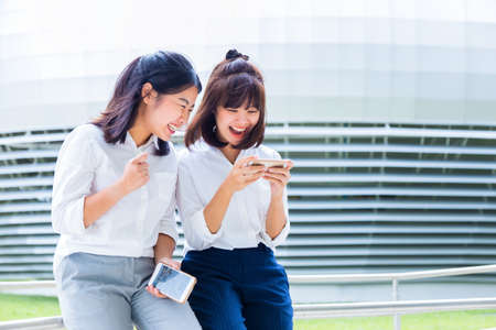 Foto de Two young Asian women enjoy social media game on their smart phones during their lunch break at their company court yard, modern office building in the background, good for modern lifestyle or happy working concept - Imagen libre de derechos