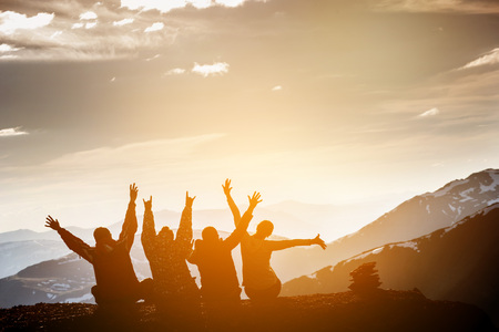 Foto de Group of friends sits on the top of mountain and having fun on mountains backdrop - Imagen libre de derechos