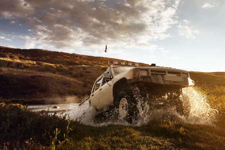 Photo pour Car SUV overcomes water on the offroad and sky background - image libre de droit