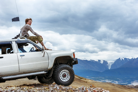 Photo for Man sits on the car SUV on the mountains background wheel - Royalty Free Image