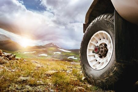 Photo pour Big car wheel on mountains and sunset backdrop. Offroad 4x4 concept - image libre de droit
