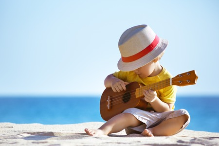 Foto de Little boy plays guitar ukulele at sea beach - Imagen libre de derechos