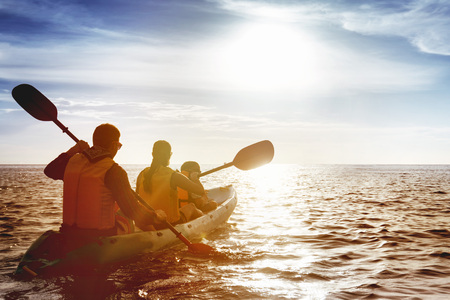 Photo for Family of father mother and son kayaking at sea sunset - Royalty Free Image