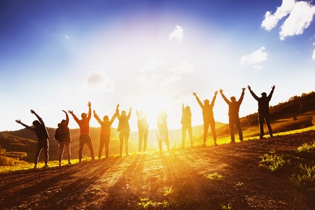 Photo pour Big group of friends raising arms on sunset together - image libre de droit