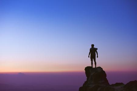 Foto de Man's silhouette at mountain top on background of sunset sky - Imagen libre de derechos