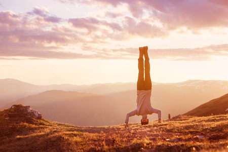 Photo for Man stands upside down at mountain sunset - Royalty Free Image