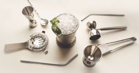 Foto de Mint julep whiskey cocktail in misted frozen metal glass and bar accessories set of jiggers on white background. Flat lay top view. Menu, alcohol recipe decor, specialized website blog design. - Imagen libre de derechos