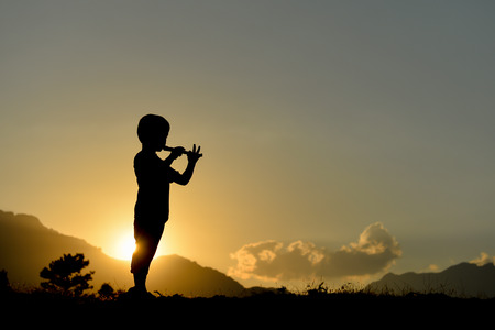 Photo for silhouette of boy playing the flute - Royalty Free Image