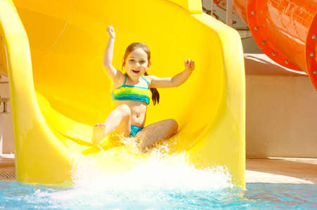 Photo for Happy little caucasian girl on waterslide of water park. - Royalty Free Image