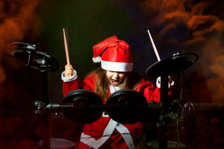 Photo for Little drummer disguised as Santa Claus playing the electronic drum kit - Royalty Free Image