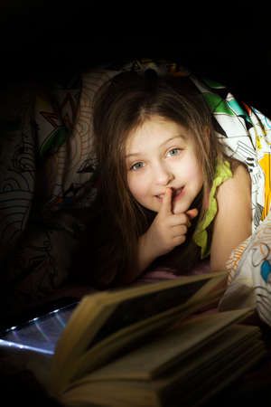 Foto de Little caucasian girl reading a book in the bed under coverlet - Imagen libre de derechos