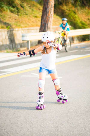 Foto de A little caucasian girl with roller quad rolling in the sun summer evening. Rollerblading and outdoor activity concept - Imagen libre de derechos