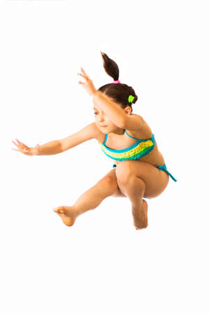 Foto de Little caucasian female 8 years old girl in multicoloured swimmwear jumping on white background. - Imagen libre de derechos
