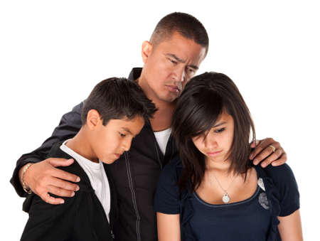 Hispanic father with kids looking down and sad on white background