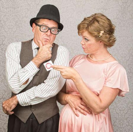 Foto de Worried man in hat with pregnant woman holding contraceptives - Imagen libre de derechos