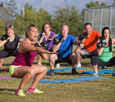 Photo for Boot camp fitness trainer yelling during squat exercises - Royalty Free Image