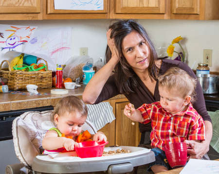 Foto de Stressed out mother in kitchen with her babies - Imagen libre de derechos