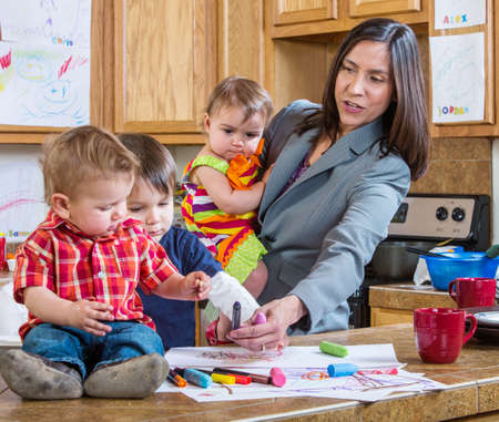 Photo pour A mother in the kitchen plays with her chilrdren - image libre de droit
