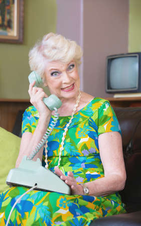 Photo pour Happy senior woman in green on rotary telephone - image libre de droit
