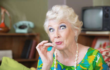 Photo for Excited Caucasian senior woman in green smoking marijuana - Royalty Free Image