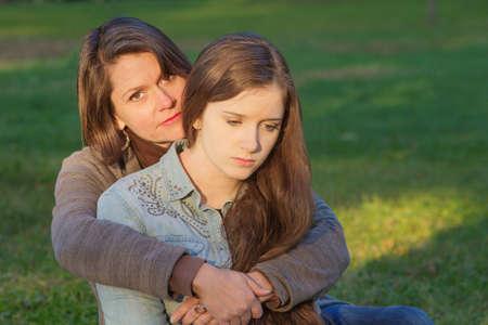 Foto de Concerned European mother holding depressed daughter outdoors - Imagen libre de derechos