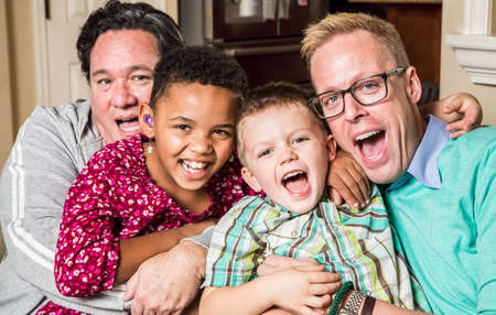 Photo pour Gay parents pose with their childen in the living room - image libre de droit