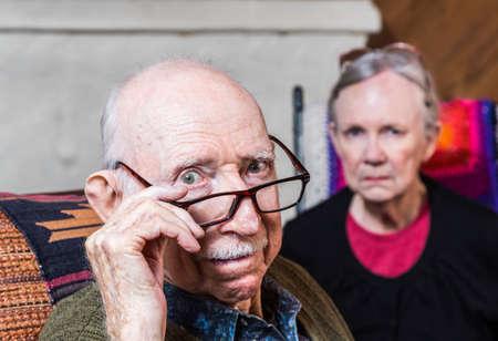 Photo pour Concerned elderly couple sitting in livingroom scowling - image libre de droit