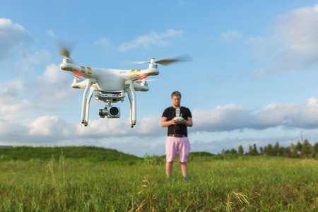 Foto de Person in field controlling drone with camera - Imagen libre de derechos