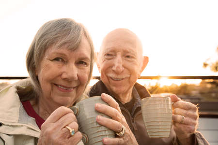 Foto per Cheerful older couple sitting outdoors with coffee - Immagine Royalty Free