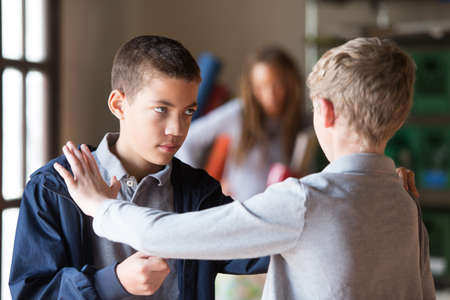 Foto de Black and white teenage male students fighting indoors. Obscured teacher in background. - Imagen libre de derechos