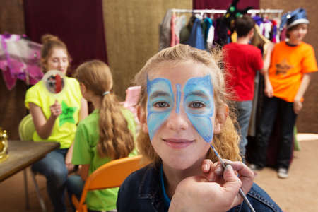 Foto de Close up view of girl getting her face painted while seated in a dressing room - Imagen libre de derechos