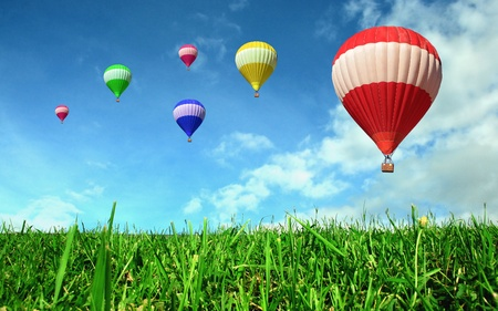 Photo for Hot air balloons floating over green field  - Royalty Free Image