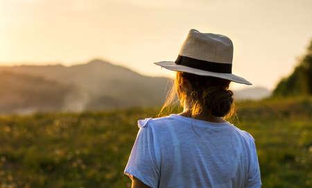 Photo pour Girl enjoying sunset view over a hill - image libre de droit