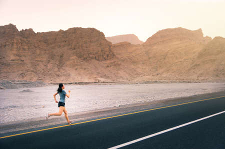 Girl running on the desert road, outdoor workout