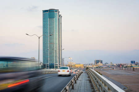 Foto per Ras Al Khaimah city scene with tower view and car passing the bridge - Immagine Royalty Free