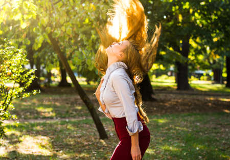 Woman swinging hair in the park, healthy and strong hair concept