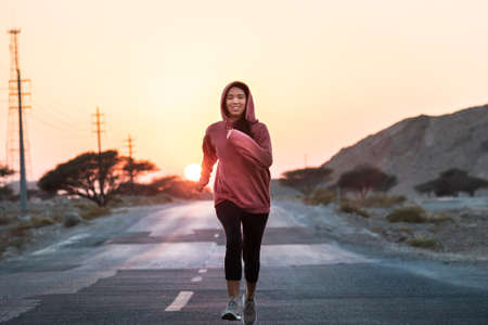 Girl running in sunset wearing a pink hoody